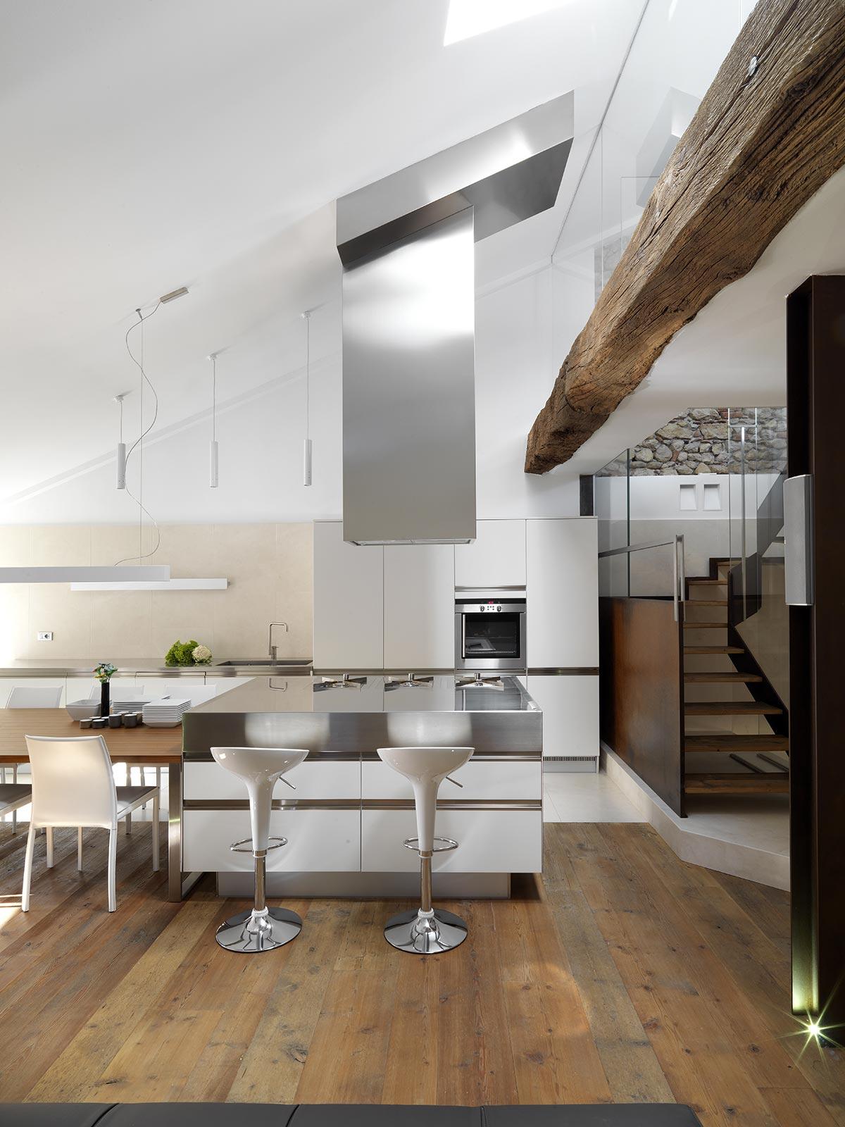 Cucina open space con isola centrale stile industriale con inox e travi in legno.