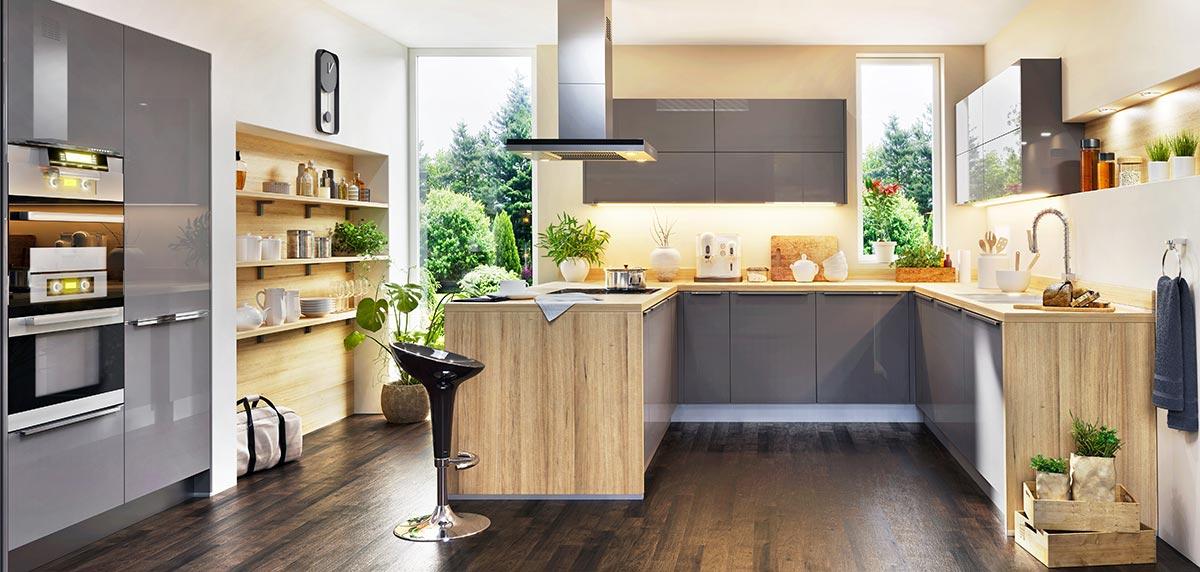 Cucina angolare moderna con penisola grigia e legno.