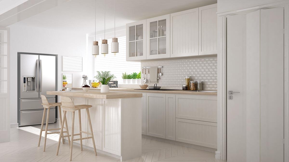 Cucina bianca con isola e top in legno chiaro.