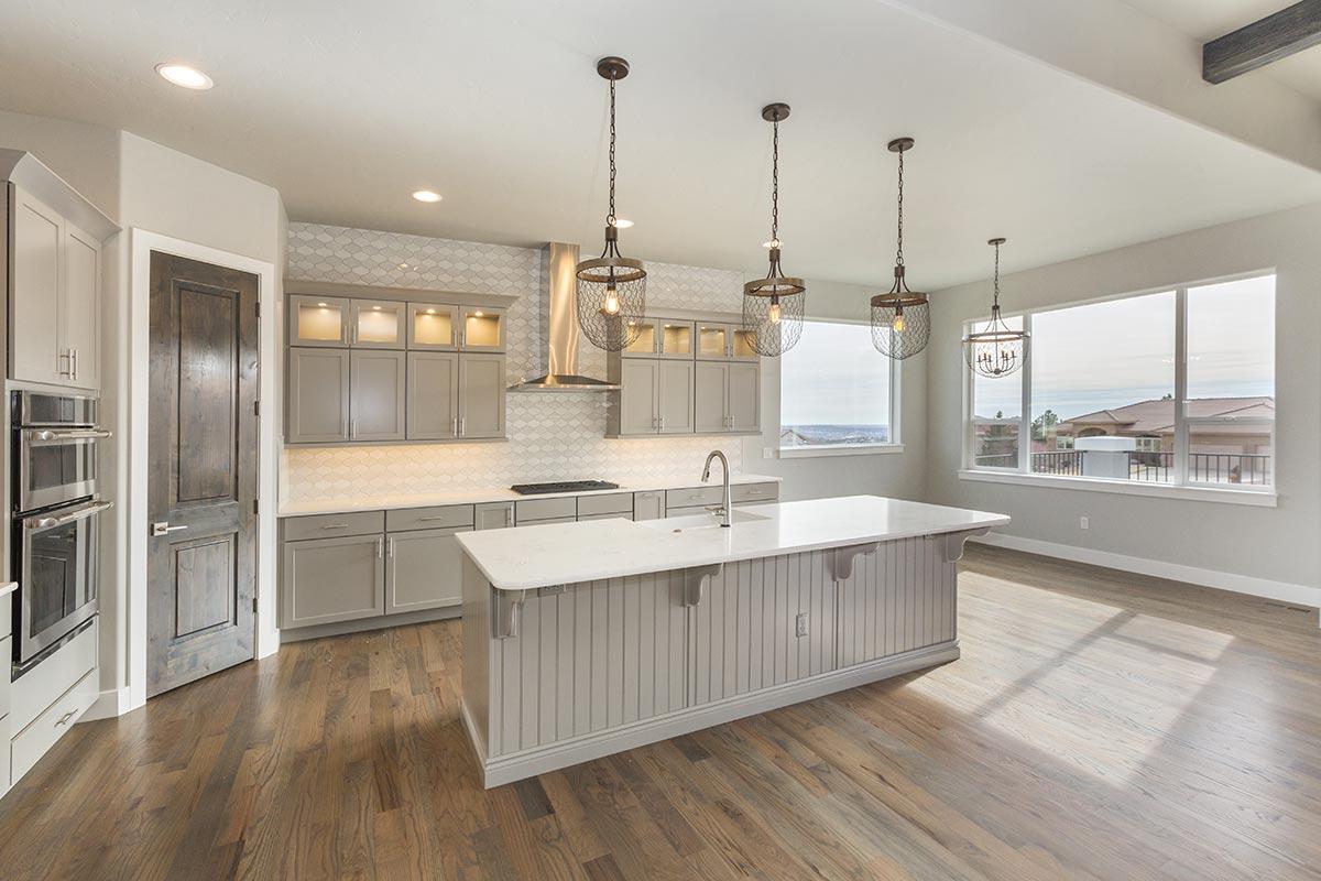 Bella cucina bianca e grigia con isola centrale con lavabo.