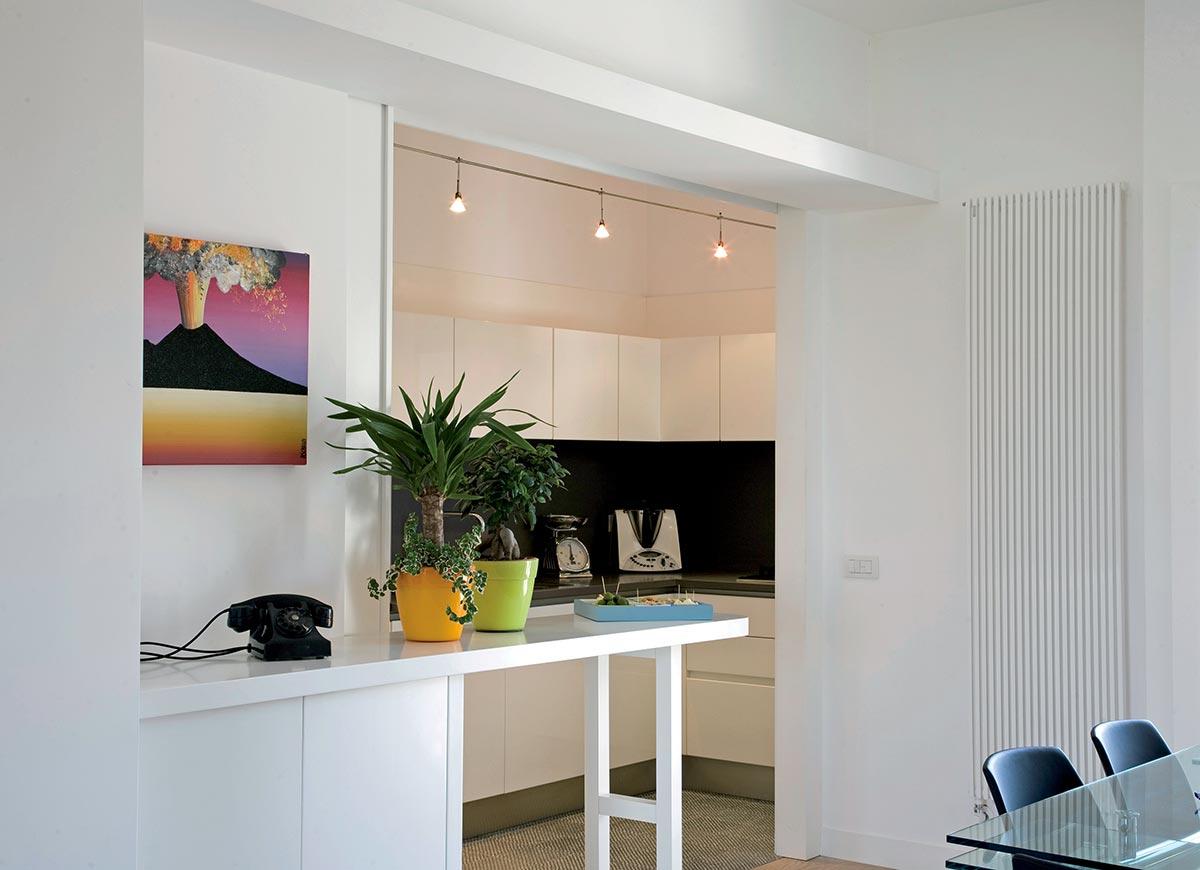 Cucina moderna bianca con penisola e vasetti colorati.