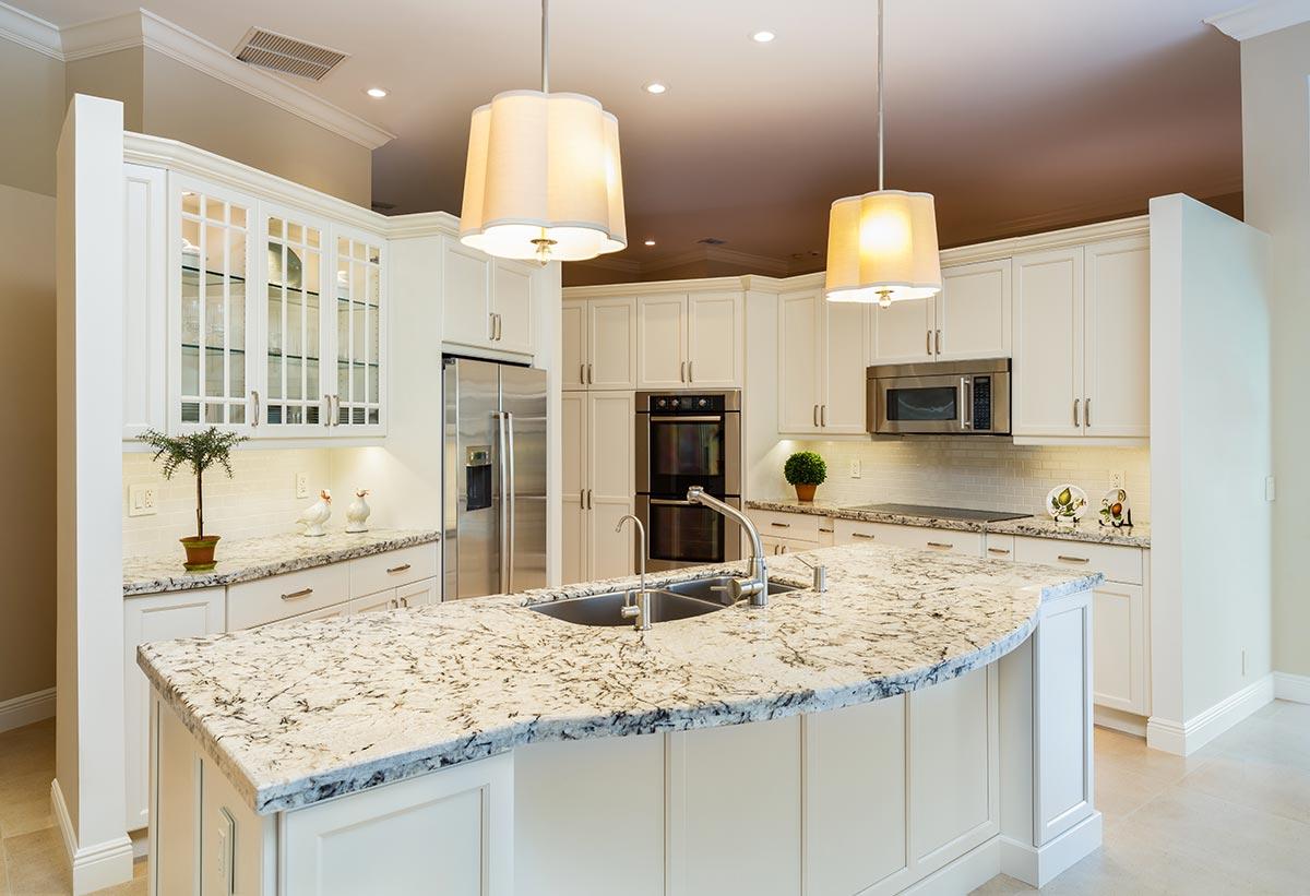 Bella cucina angolare con isola centrale e top in marmo.