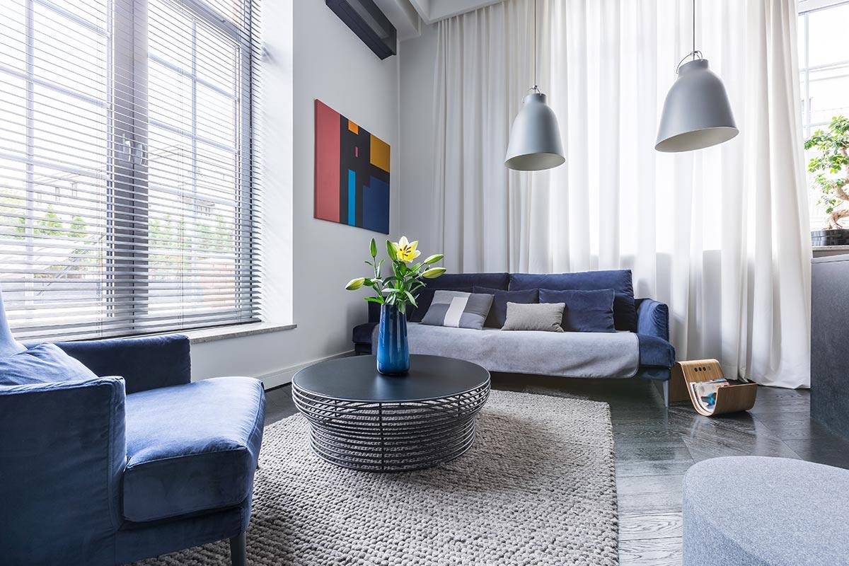Piccolo salotto moderno arredato con colori blu, grigio e bianco.