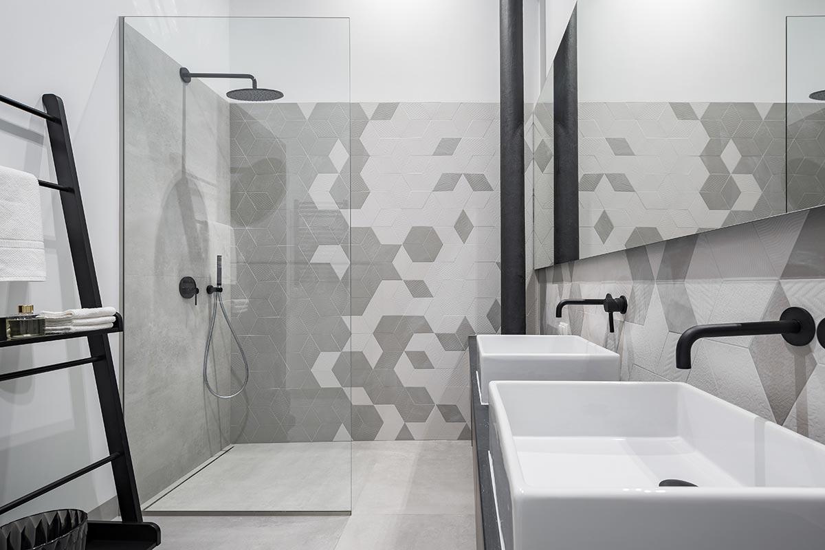 Bagno piccolo con doccia in vetro trasparente e mattonelle design.