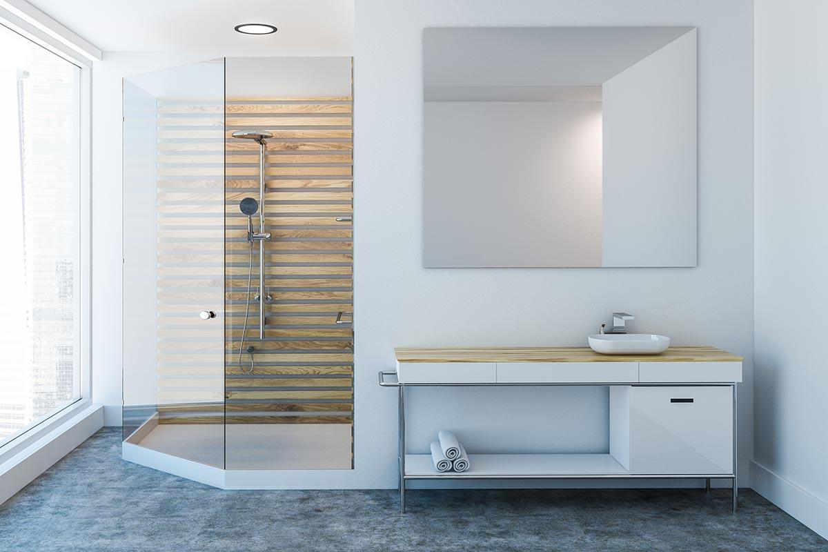 Bagno bianco con doccia angolare e parete in legno.