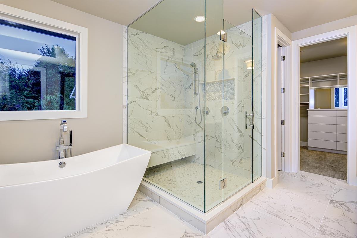 Bagno con vasca design e rivestimento interno doccia in marmo.