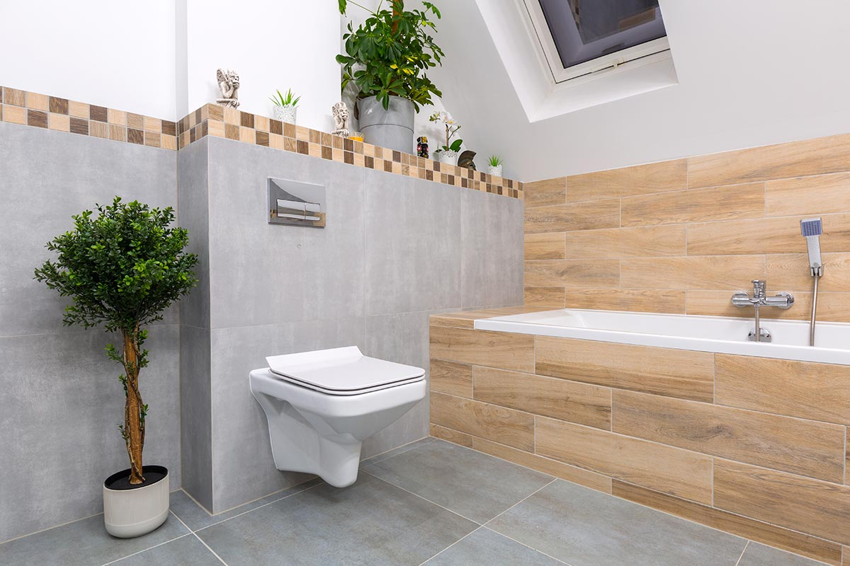 Bagno moderno con parete con piastrelle grigie e vasca rivestito con piastrelle effetto legno.