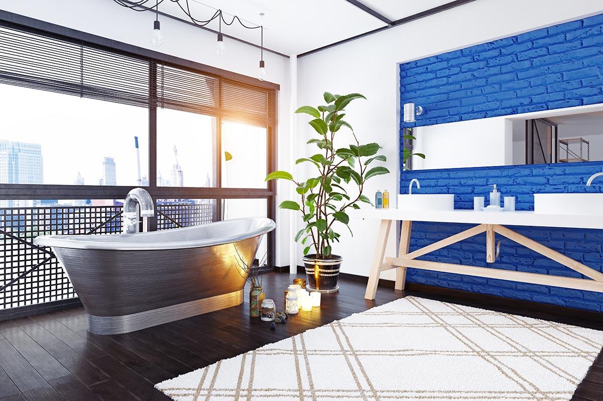 Bagno moderno con vasca nera e bianca e parete in mattoni color blu.