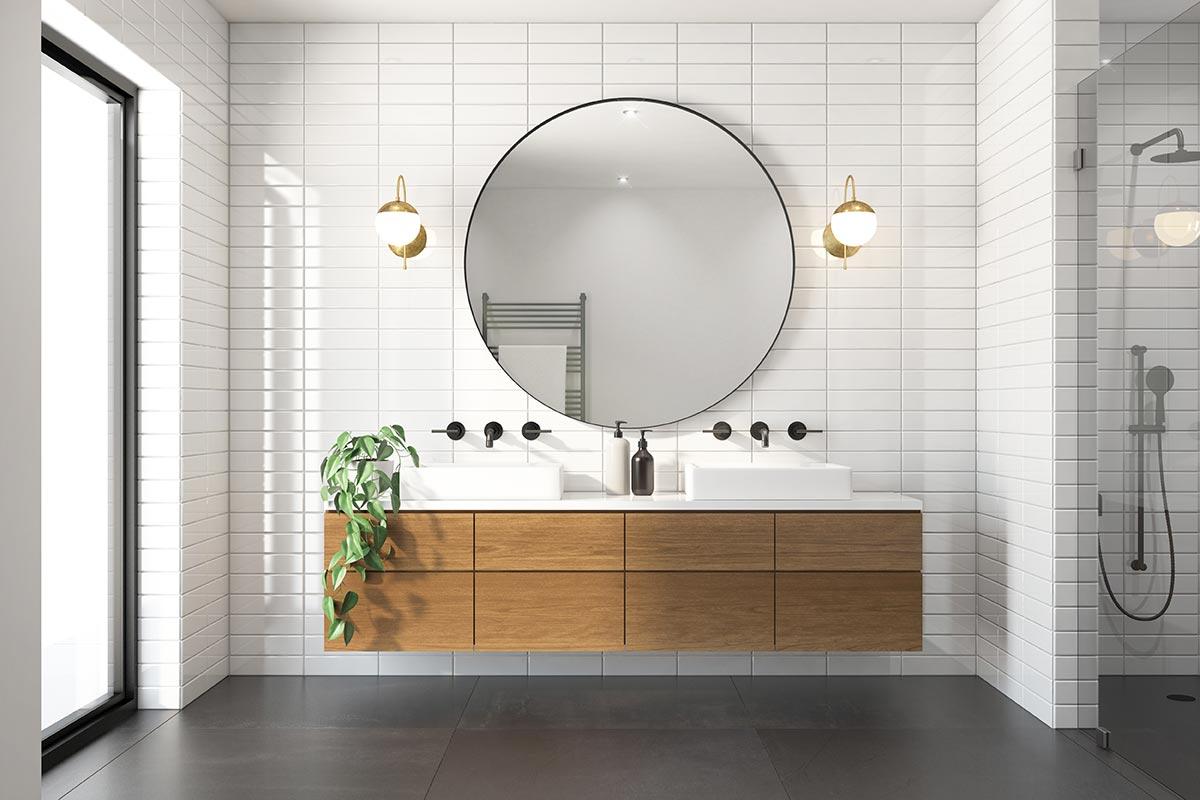 Bagno moderno con mobile lavabo in legno sospeso e grande specchio rotondo.