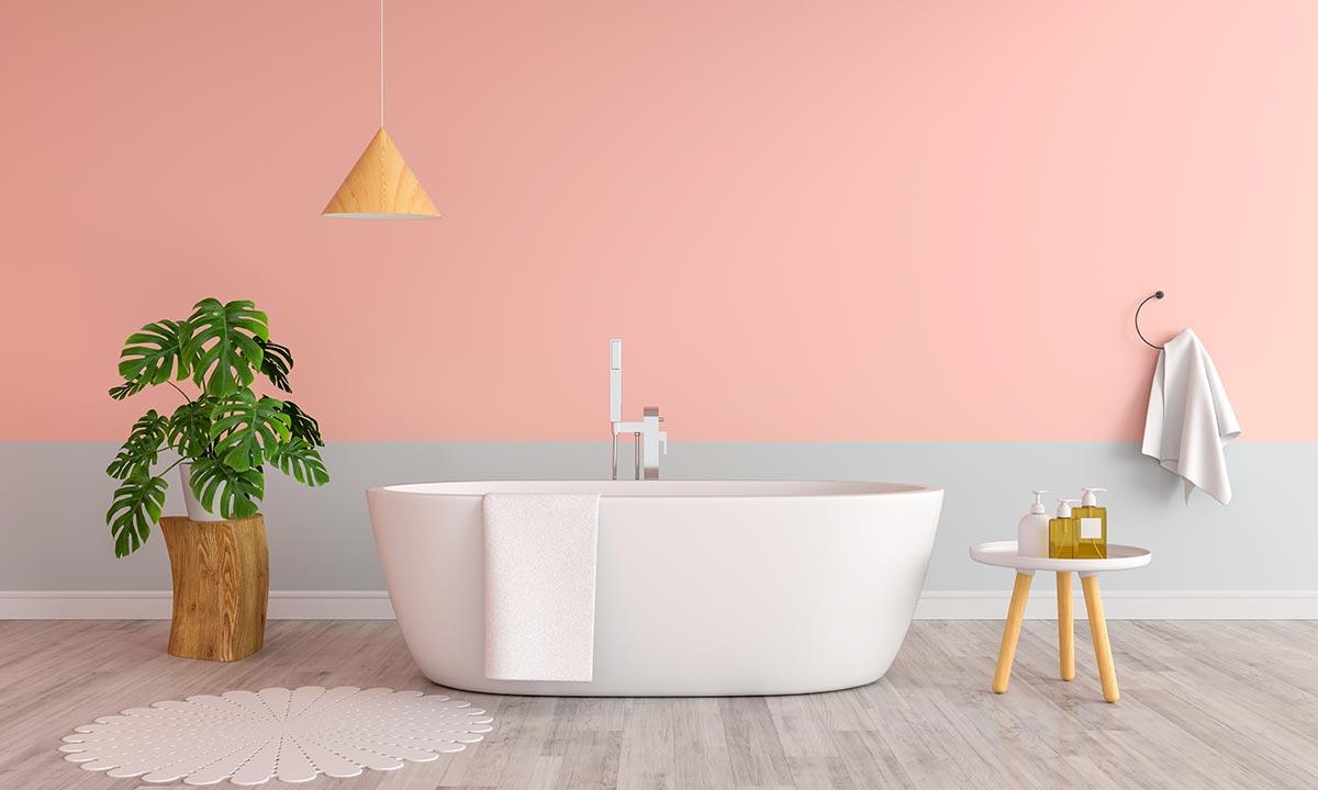 Bagno moderno con parete rosa e grigia con vasca bianca.