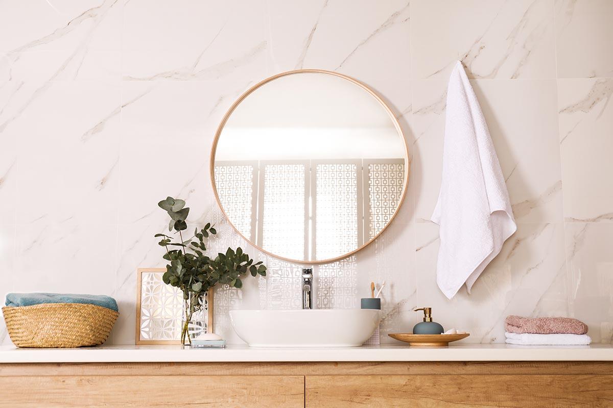 Mobile bagno moderno in legno con specchio tondo e cornice dorata.