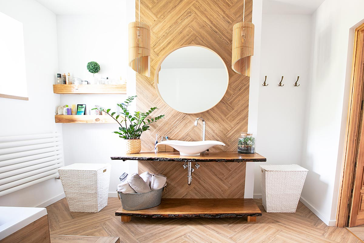 Bellissimo bagno in stile moderno con mobile lavabo in legno naturale, parete in legno e specchio rotondo.