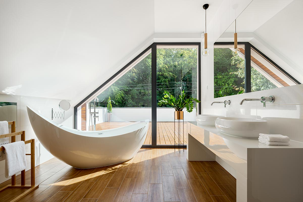 Bellissimo bagno stile moderno con vasca design e pavimento effetto legno.