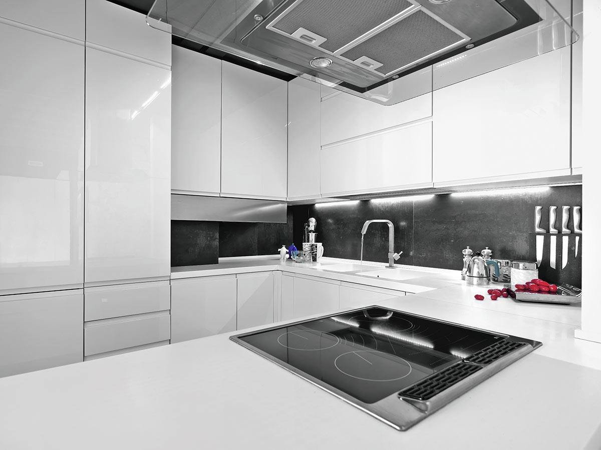 Cucina moderna bianca lucida con piastrelle e piano cottura nero.