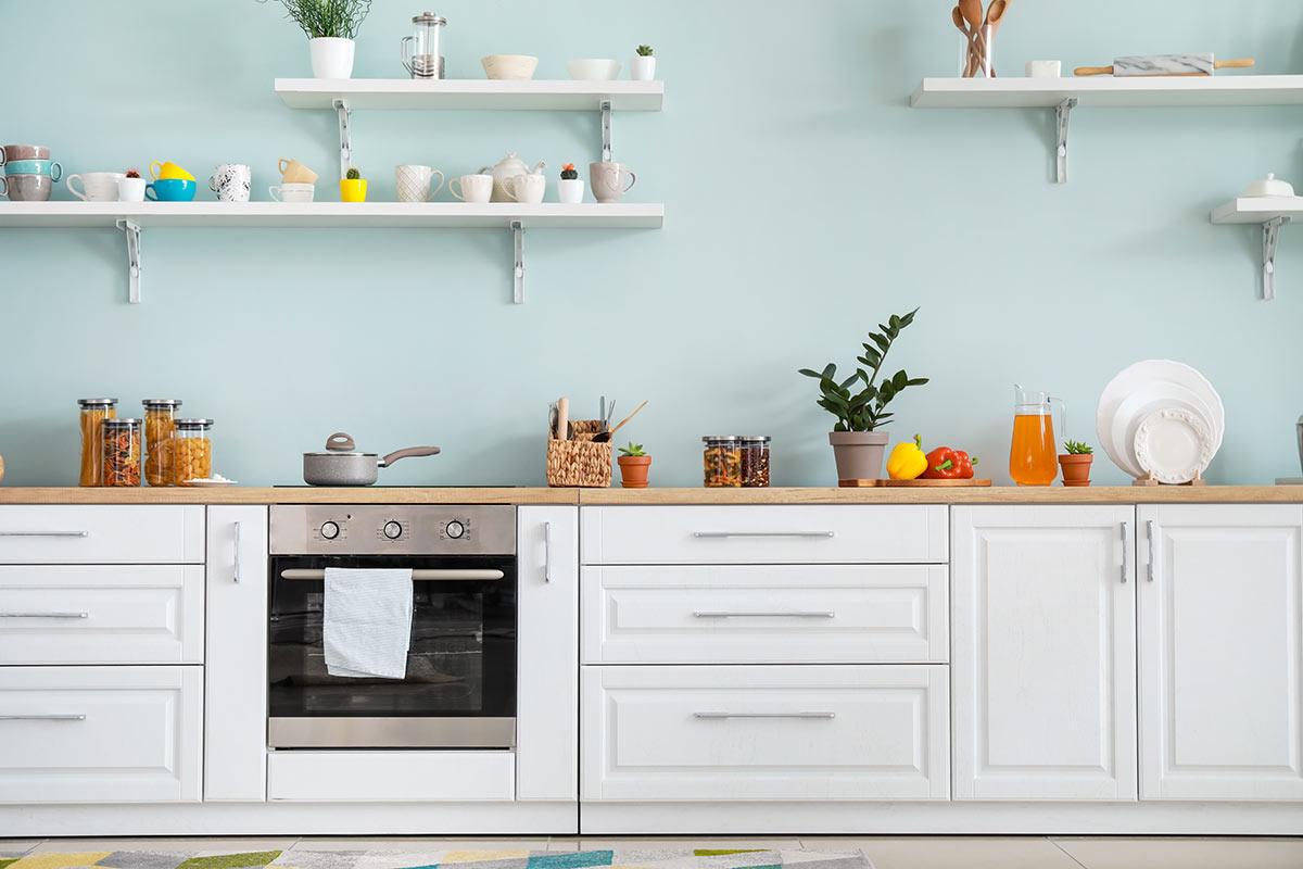 Cucina lineare con parete celeste, ideale in un ambiente moderno.
