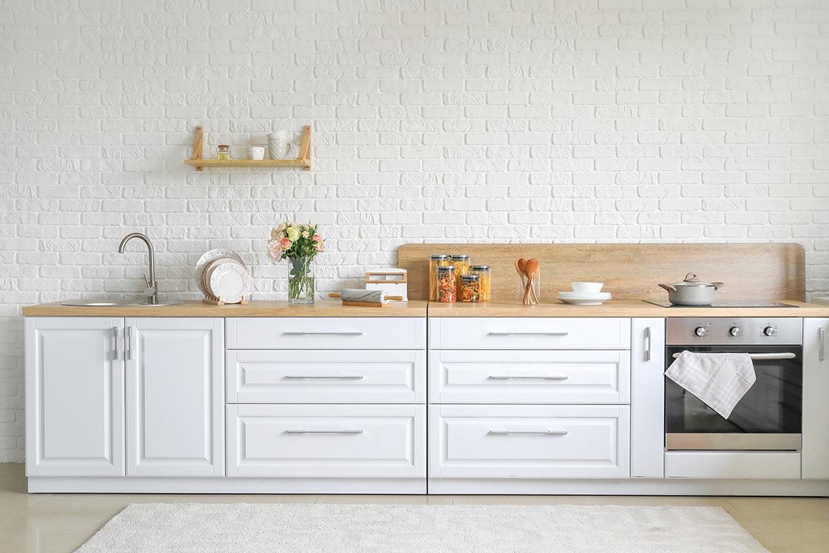 Cucina bianca moderna con piano lavoro legno e parete rivestita di mattoni bianchi.