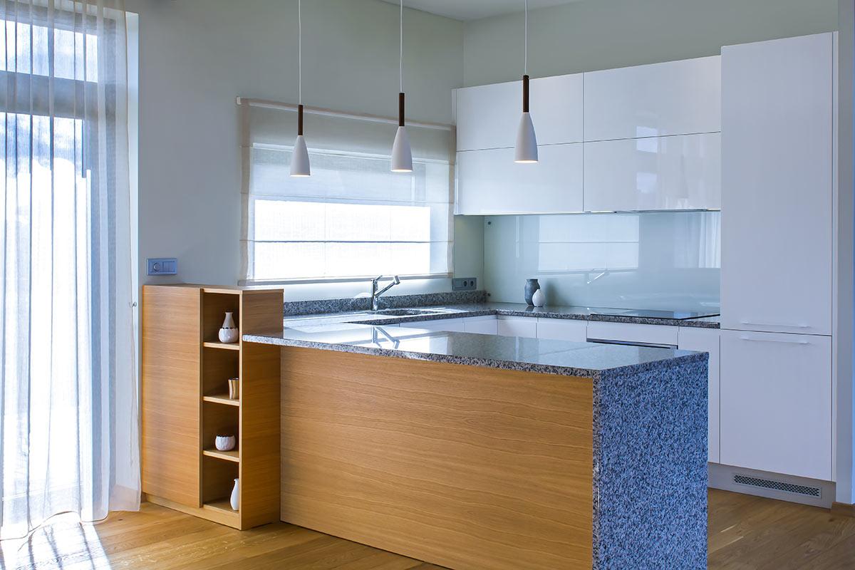 Cucina bianca con marmo blu stile moderno con penisola rivestita con pannello in legno lato soggiorno.