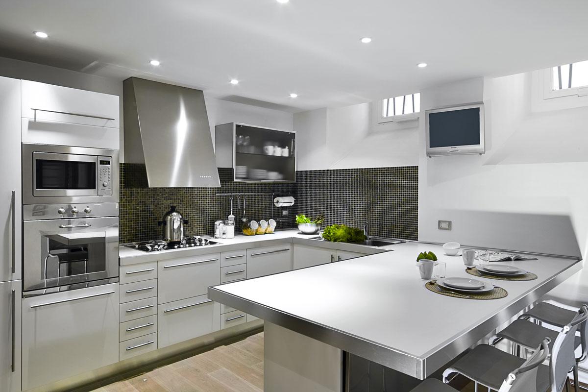Cucina moderna con penisola bianca e inox.