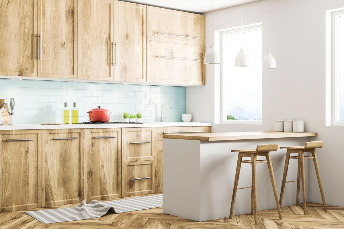 Splendida cucina in legno chiaro con penisola realizzata in muratura e due sgabelli in legno.