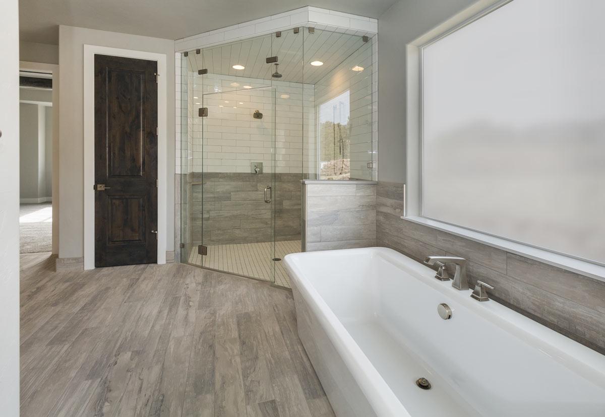 Bagno con vasca e doccia con box in vetro trasparente, pavimenti in piastrelle effetto legno.