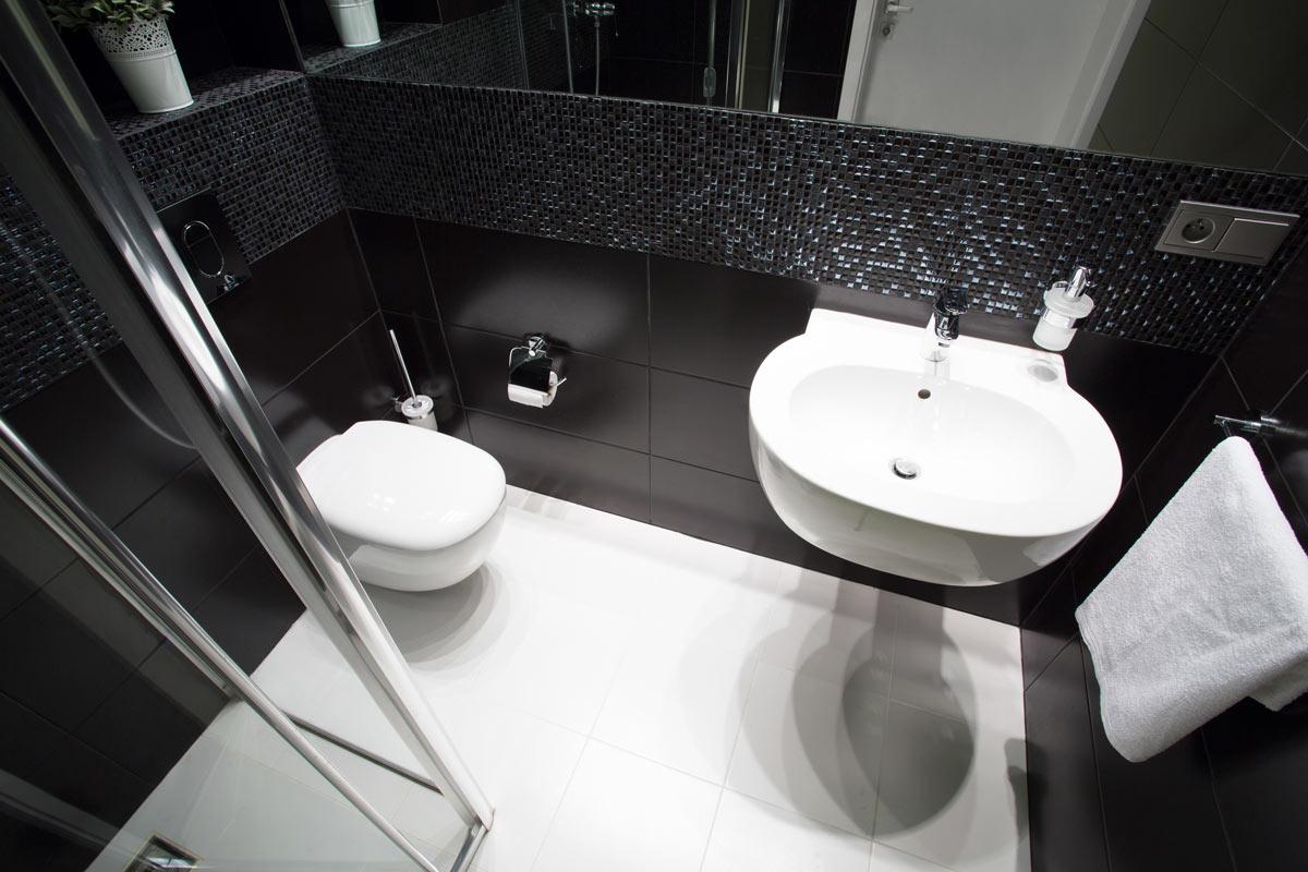 Un bagno piccolo rinnovato con piastrelle nere e bianche, stile moderno.