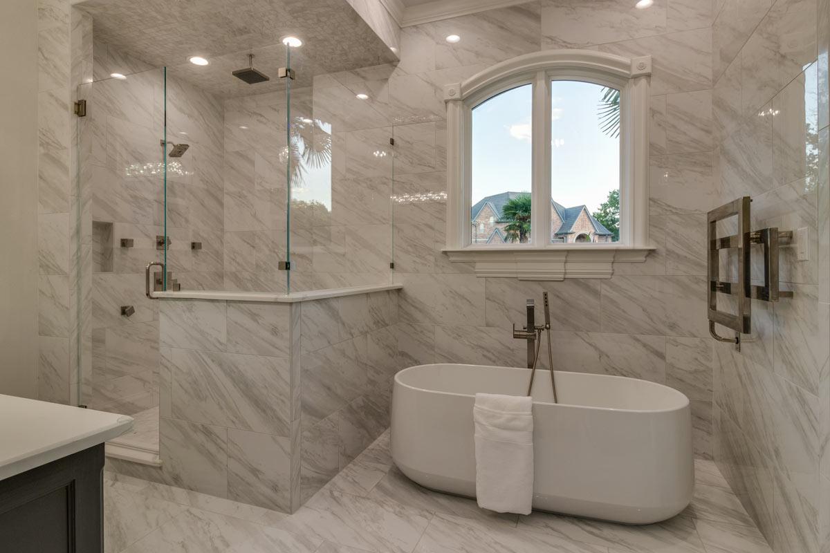 Bagno moderno ristrutturato con marmo sulle pareti.