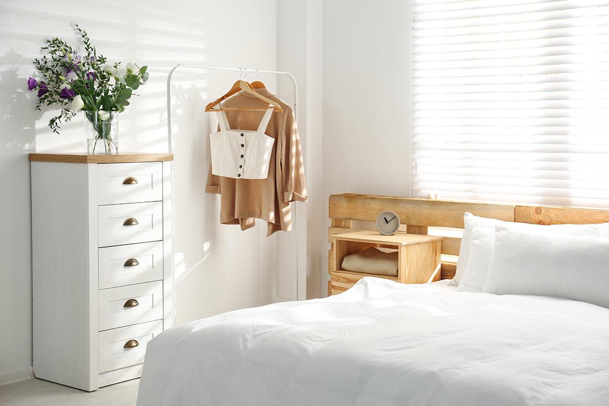 Camera moderna con settimino bianco e top in legno, testata letto con pallet.
