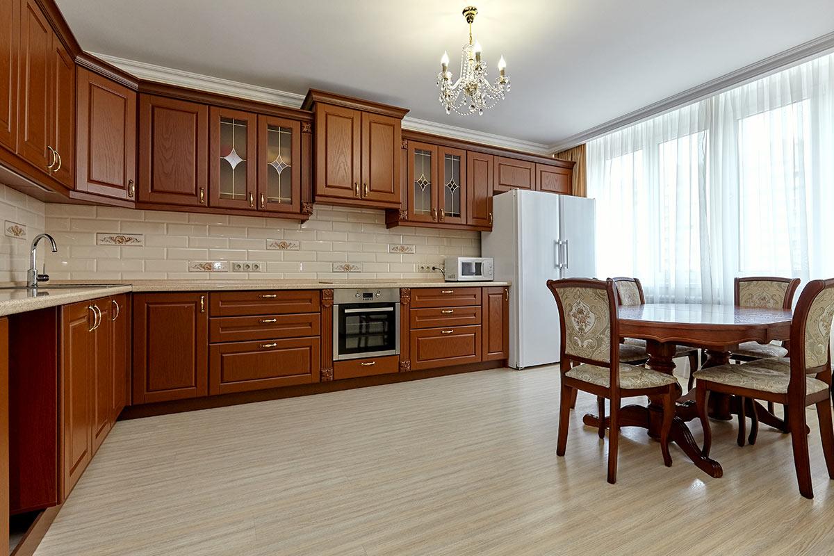 Cucina in legno angolare con mattonelle beige.