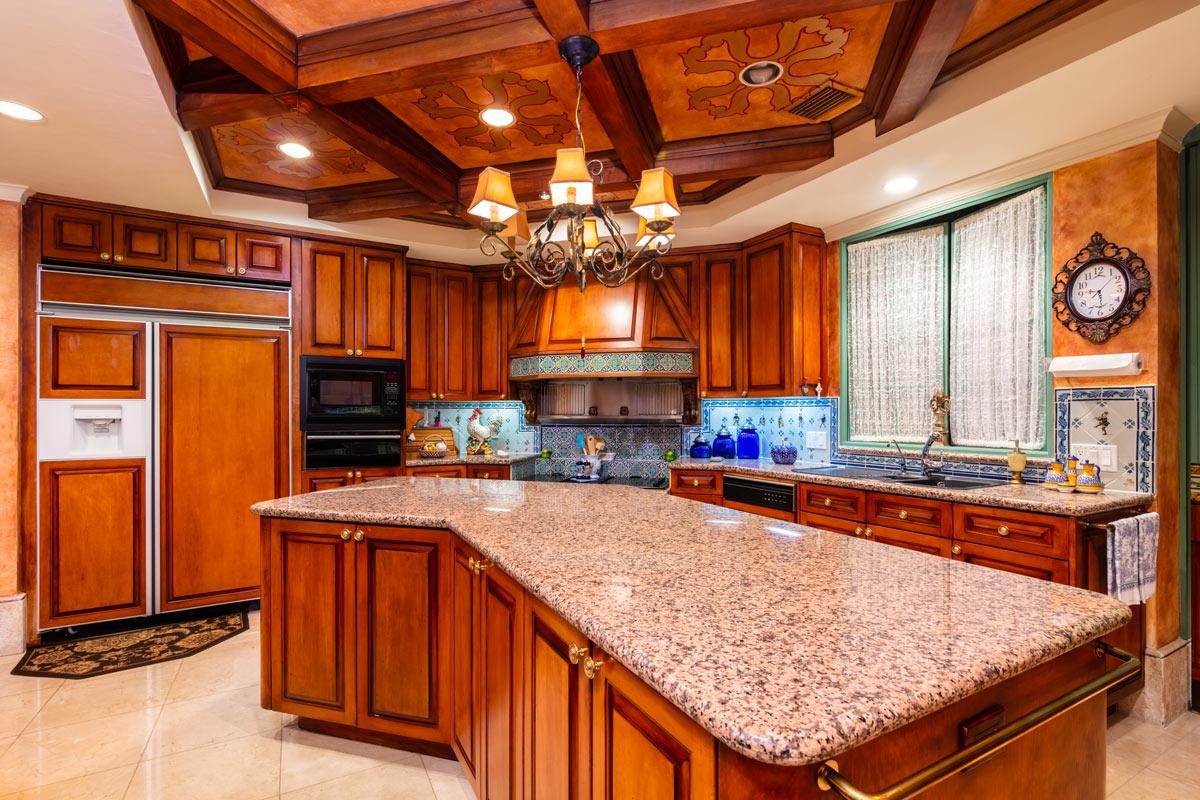 Cucina in legno con isola e top in marmo.