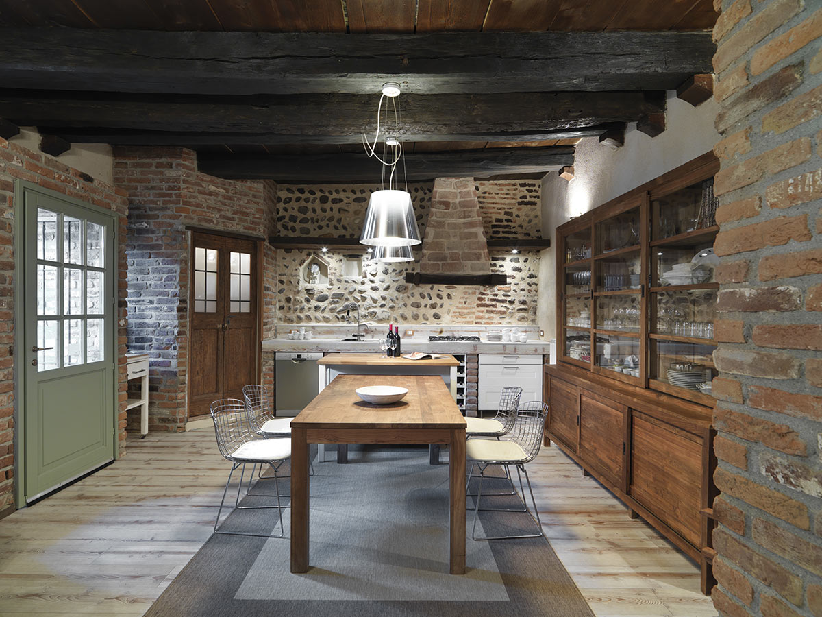 Cucina rustica in muratura con parete rivestite in pietra e credenza in legno naturale.