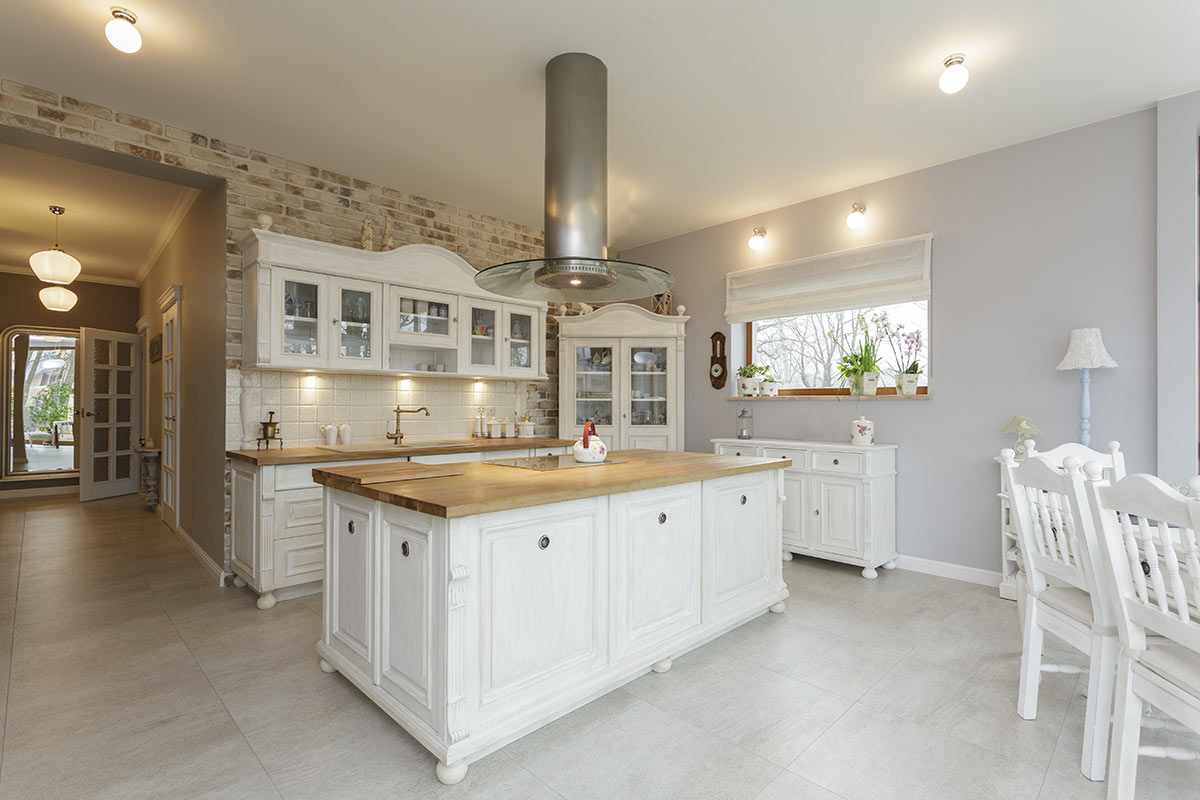 Bellissima cucina bianca e legno con isola centrale e cappa sospesa.