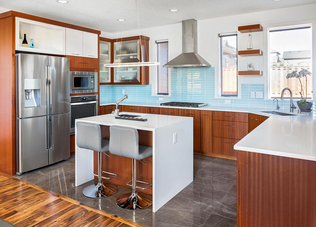 Cucina moderna con piccola isola centrale, legno e azzurro.
