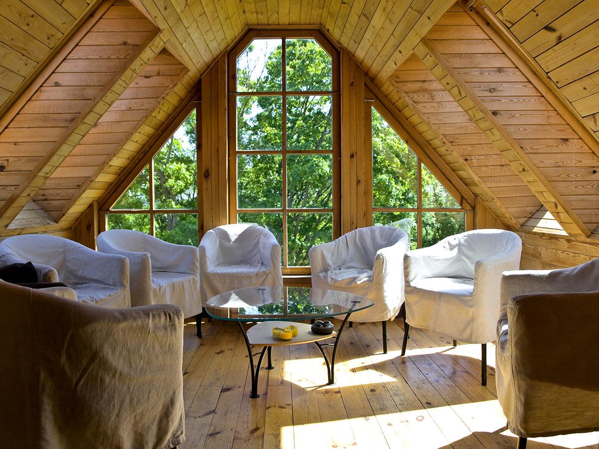 Bellissima mansarda in legno con grande finestra.