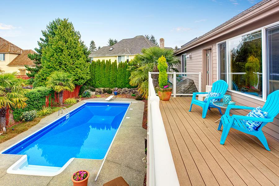 Piccolo giardino con piscina interrata rettangolare.