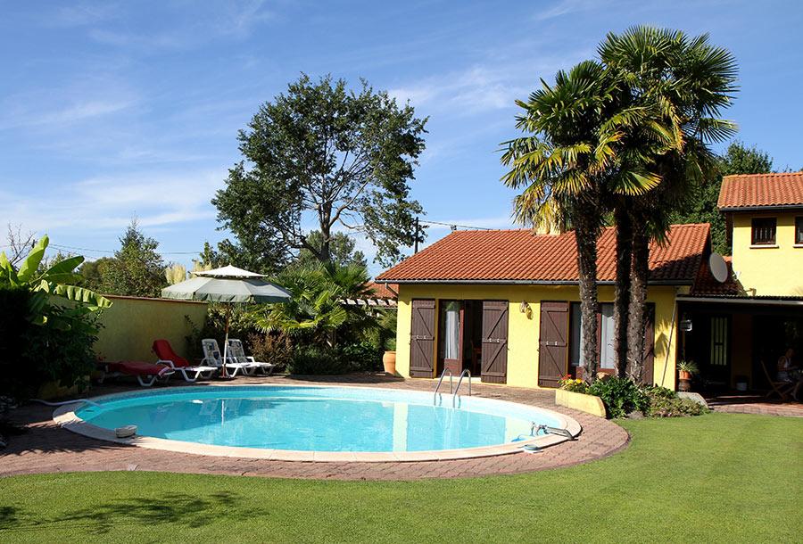 Grande piscina rotonda interrata in acciaio in giardino dietro casa.