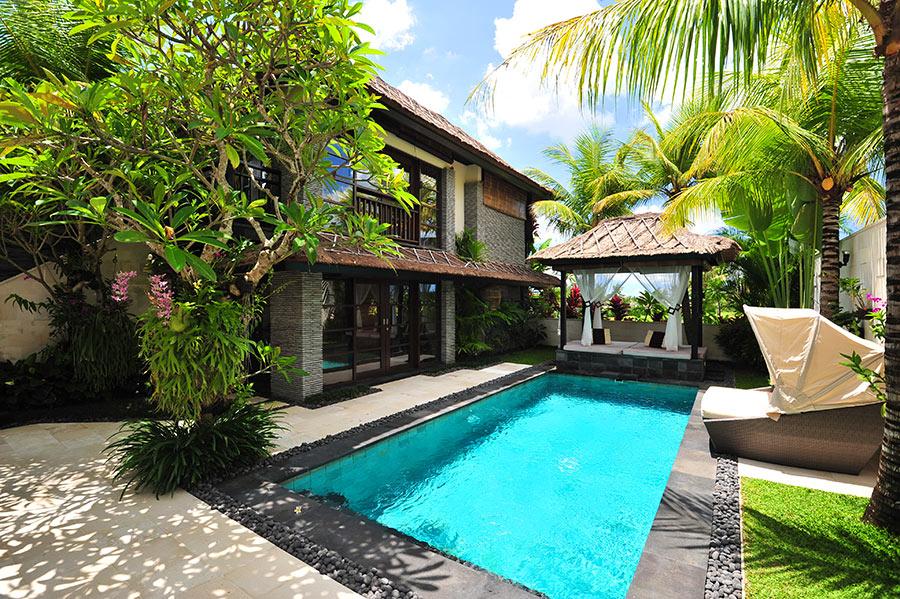 Piscina in acciaio in un piccolo giardino circondato di alberi e palme.