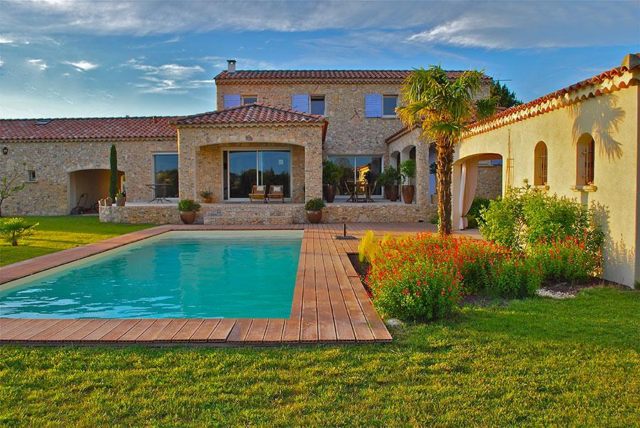 Grande casa in pietra con giardino e piscina rettangolare con bordi in legno.