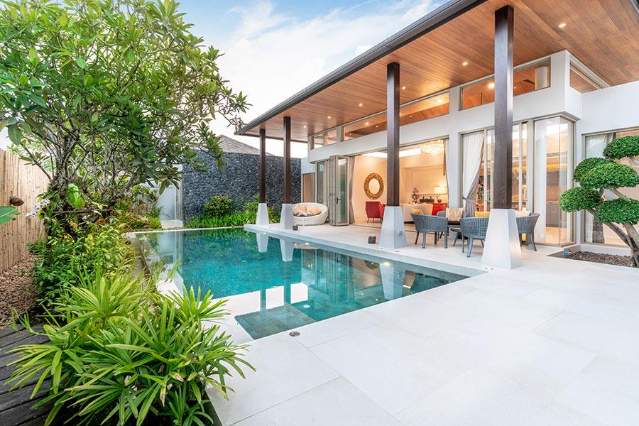 Casa con terrazzo e piscina interrata rettangolare rivestita di piastrelle.