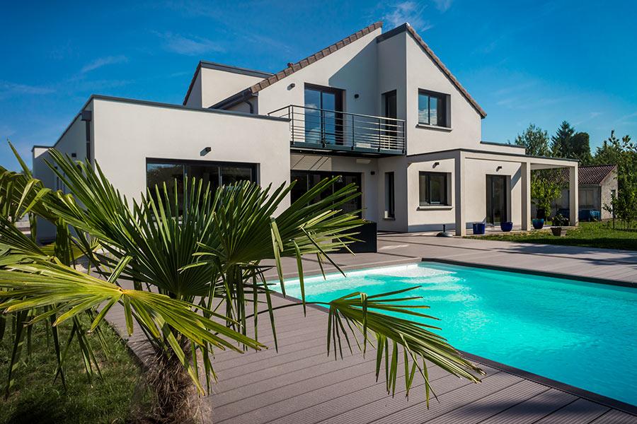 Villa bianca con piscina interrata con pannelli in acciaio rettangolare.