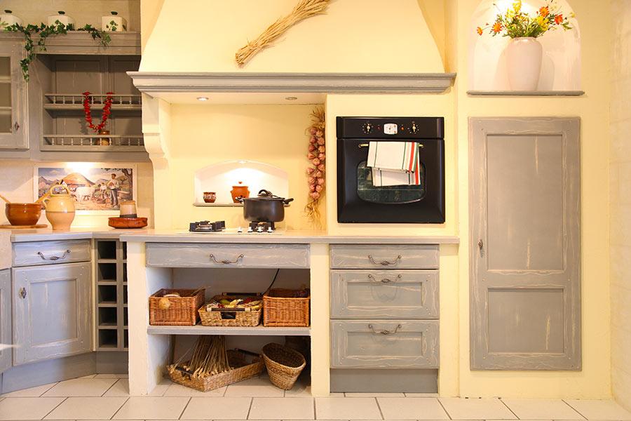 Cucina in muratura stile country con sportelli effetto invecchiato.