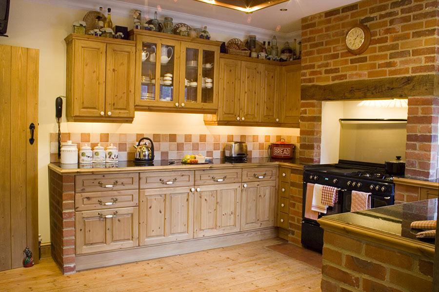 Cucine in muratura rustiche con mattoncini rossi e mobili in legno.