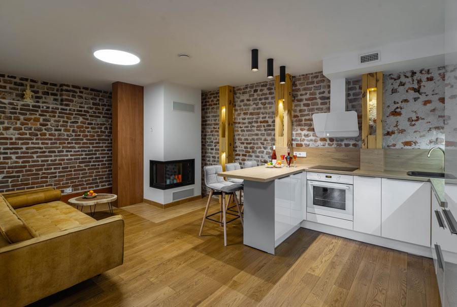 Cucina moderna con pareti con mattoni a vista e pavimento in finto legno.