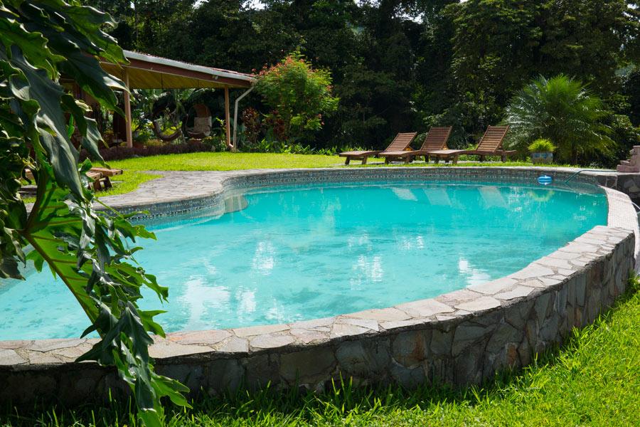 Dislivello in giardino con piscina seminterrata.