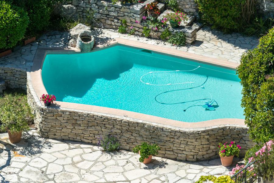 Piscina seminterrata con rivestimento esterno in pietra naturale, collocata in giardino sfruttando un dislivello.