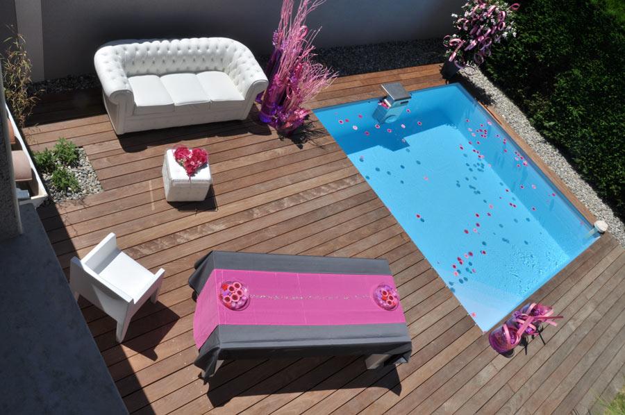 Piccola piscina rettangolare seminterrata collocata in terrazzo con pavimento in legno.