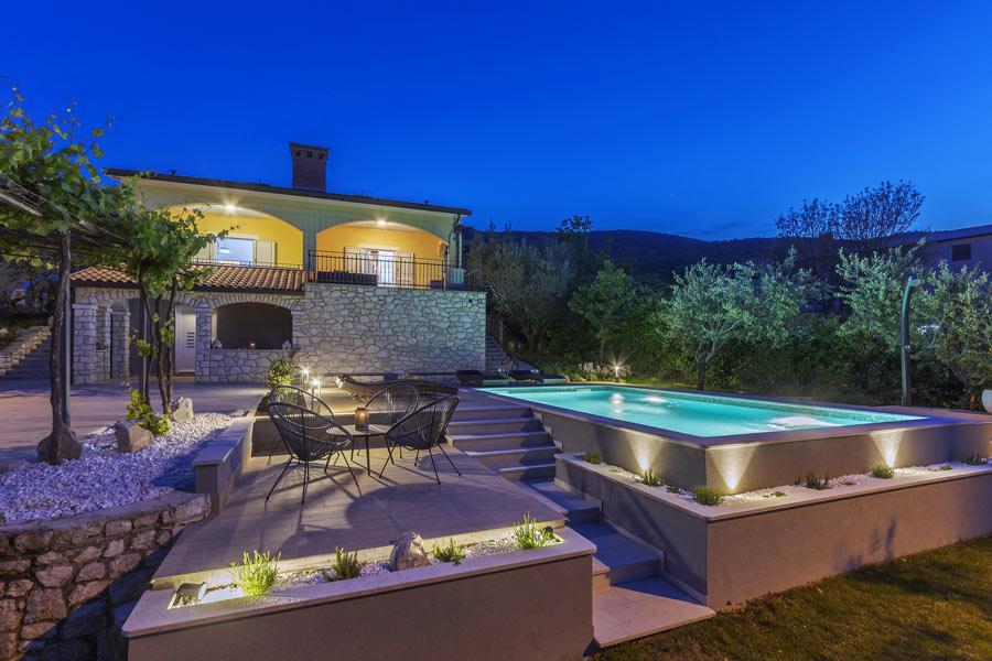 Casa in pietra con grande terrazzo e piscina seminterrata.
