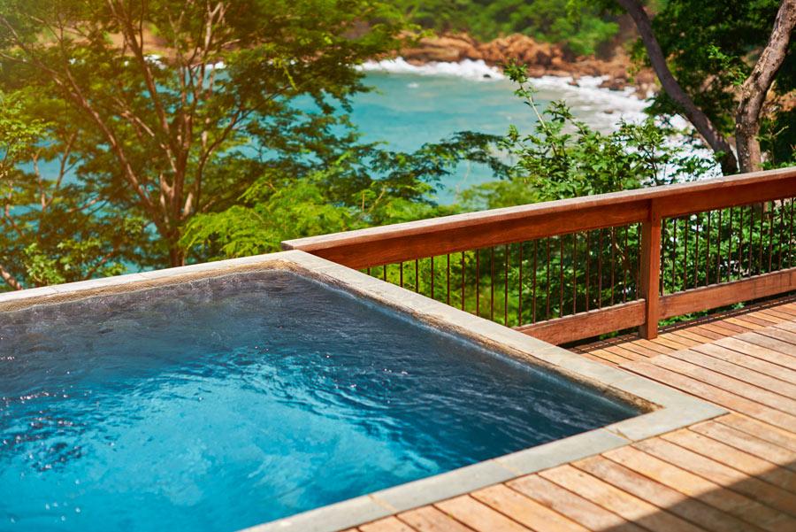 Piccola piscina quadrata su terrazzo in legno.