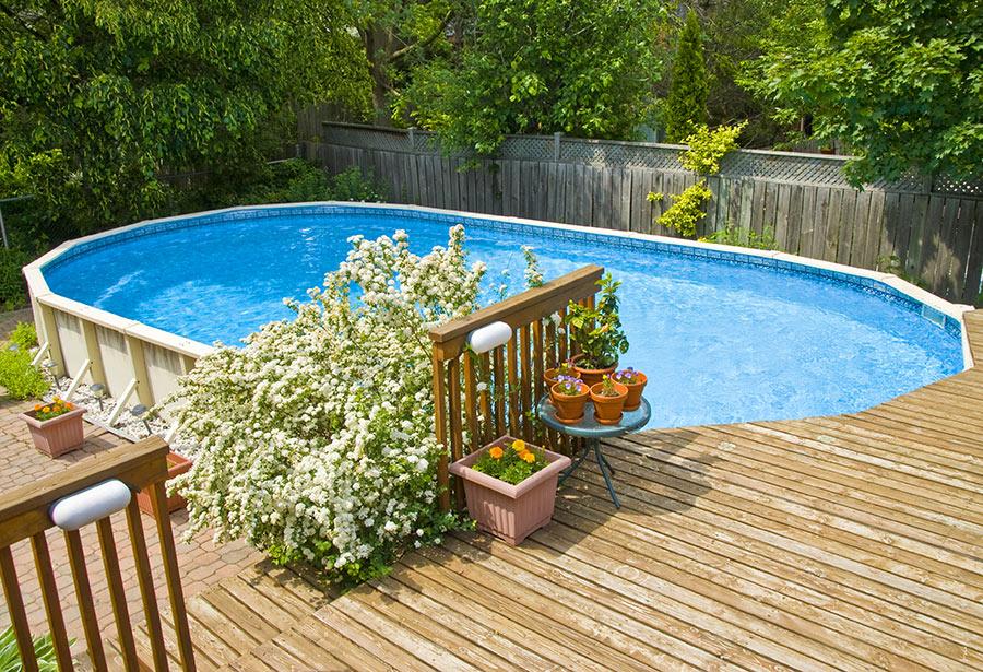 Piscina fuori terra rettangolare con effetto seminterrato grazie all'altezza del terrazzo in legno.