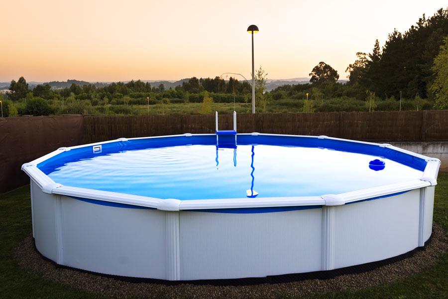 Giardino con piscina rigida bianca fuori terra al tramonte.
