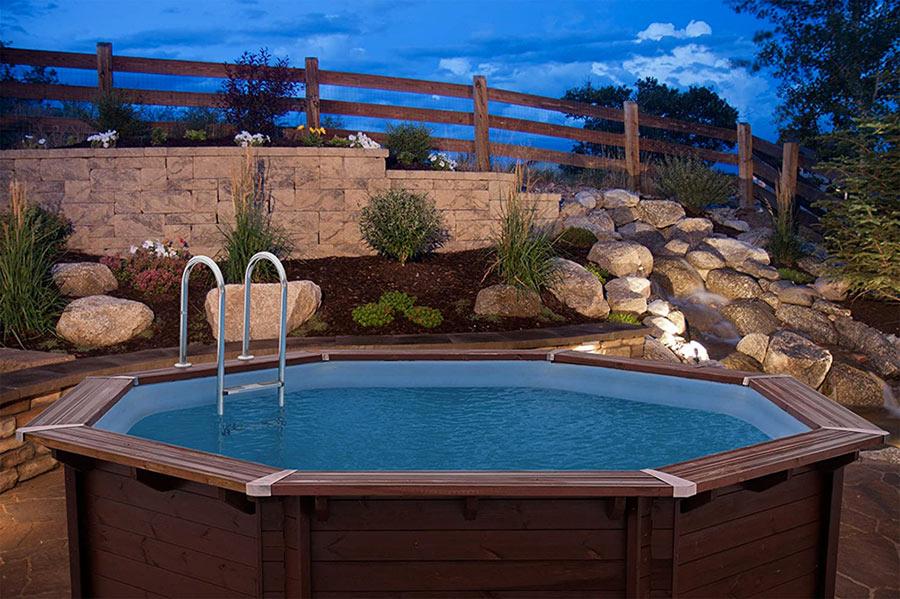 Giardino con aiuola di pietre e piscina in legno.
